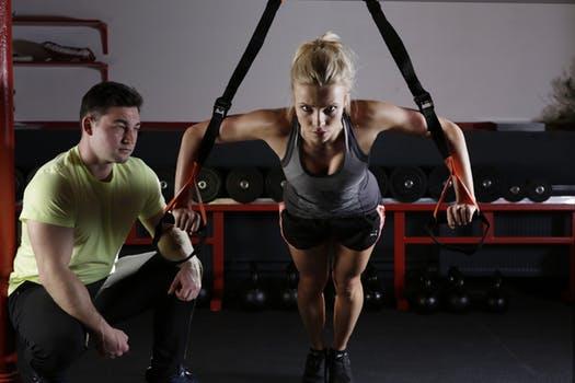 Frau trainiert mit Trainer an TRX-Seilen.